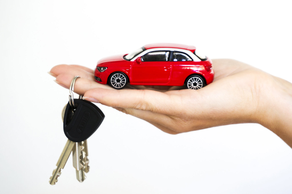 a toy car on the hand with the keys hanging the finger